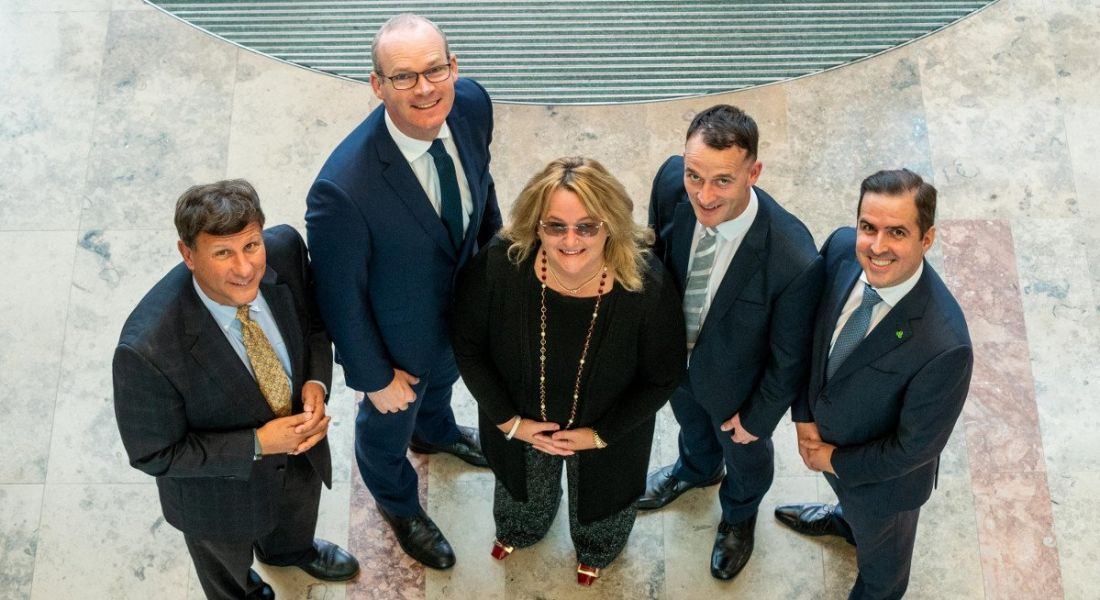 A group of four men in suits and one woman in business attire are standing together looking upwards at the camera and smiling.
