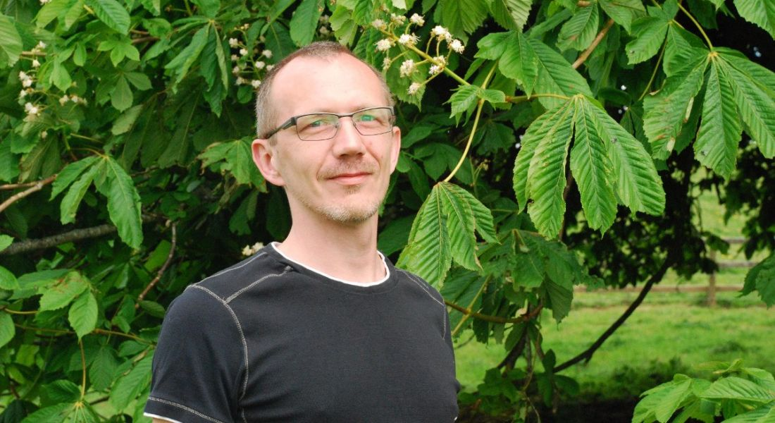 A man is standing against a backdrop of leaves outside, looking into the camera.