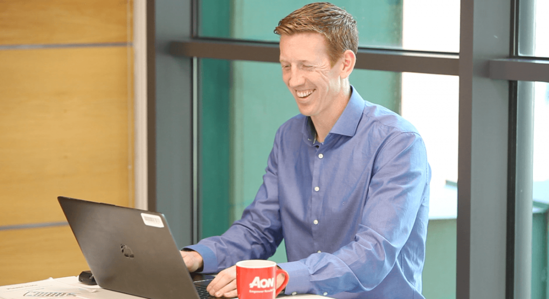A man in business attire is sitting at a table using his laptop and smiling.