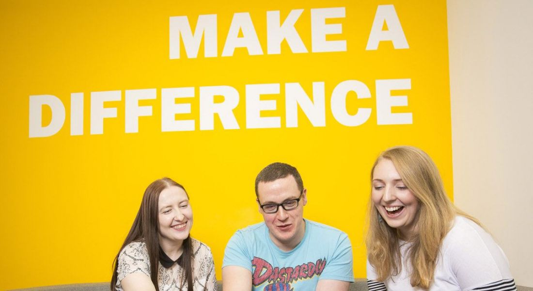 Three young professionals are smiling and interacting, sitting in front of a yellow wall with white writing that says 'make a difference'.