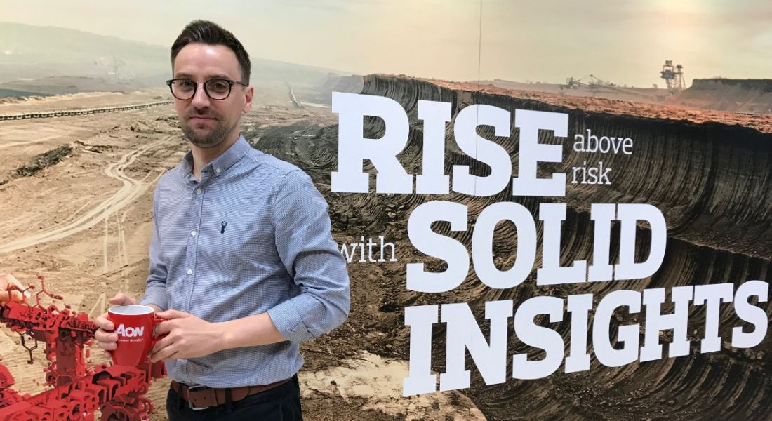 A young professional man is standing against a wall decorated with mountain imagery reading 'rise above risk with solid insights', looking into the camera and holding a red Aon-branded cup.