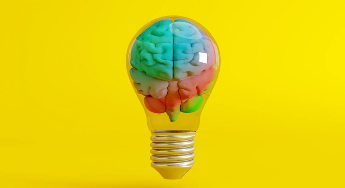 Colourful brain inside a lightbulb on yellow background.