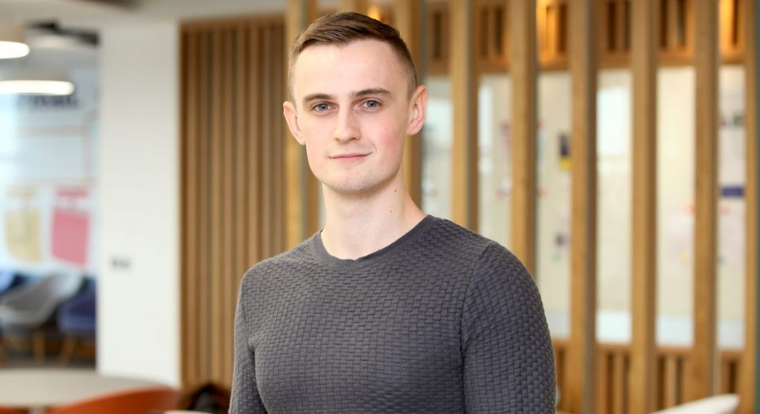 Headshot of a young man in smart casual clothes looking into the camera in a modern corporate setting at Liberty IT, Belfast.