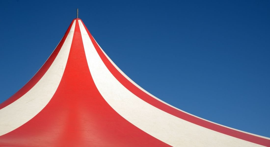Red and white striped circus tent against a blue sky.