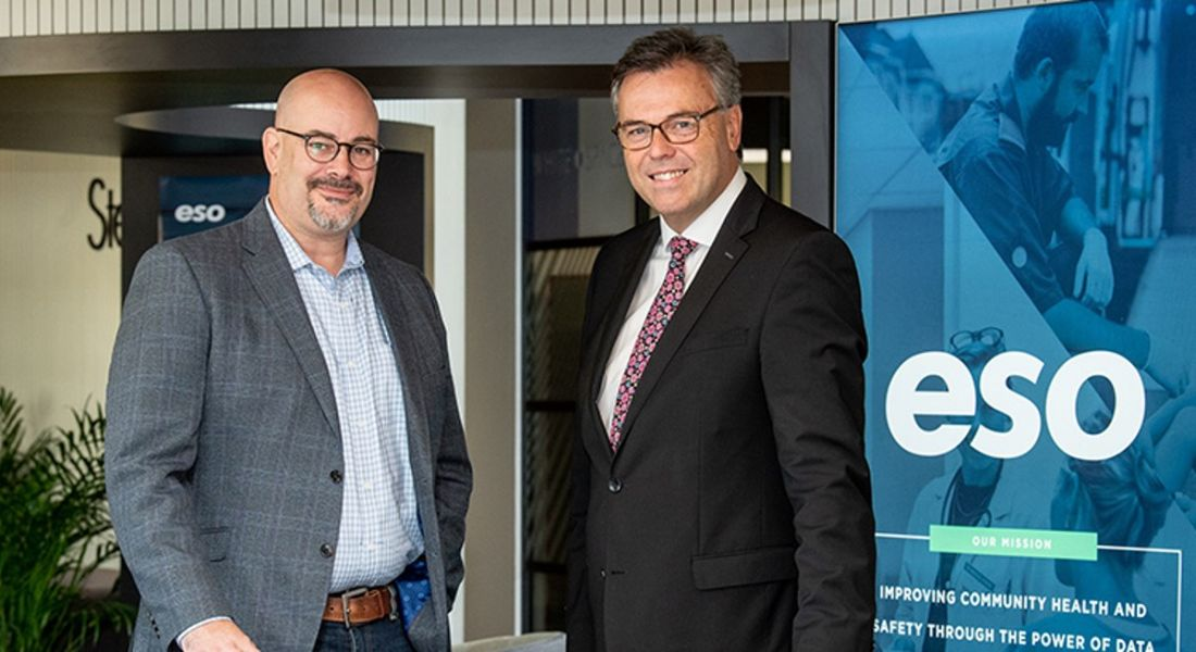 Two men in business attire standing side by side smiling at camera with ESO logo in background.