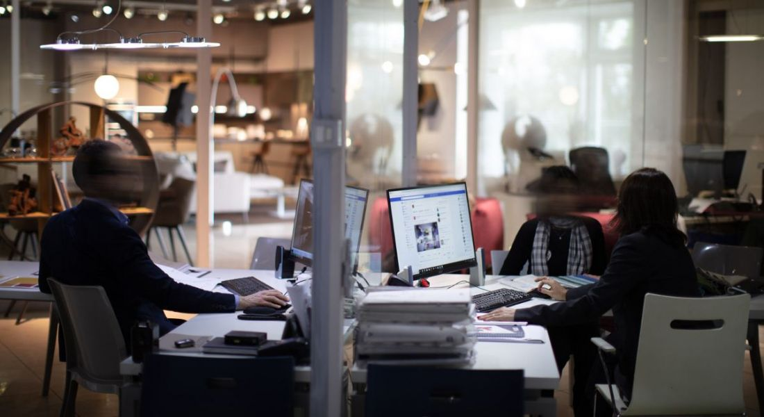 Blurred photo of a modern office space with people working at computers.