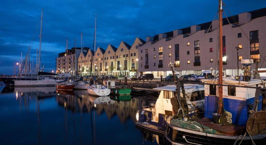 The harbour of Galway city at night with boats docked in front of a row of buildings.