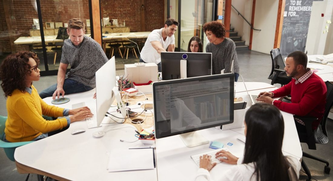 Casually dressed business team working at desks in a modern open-plan office.