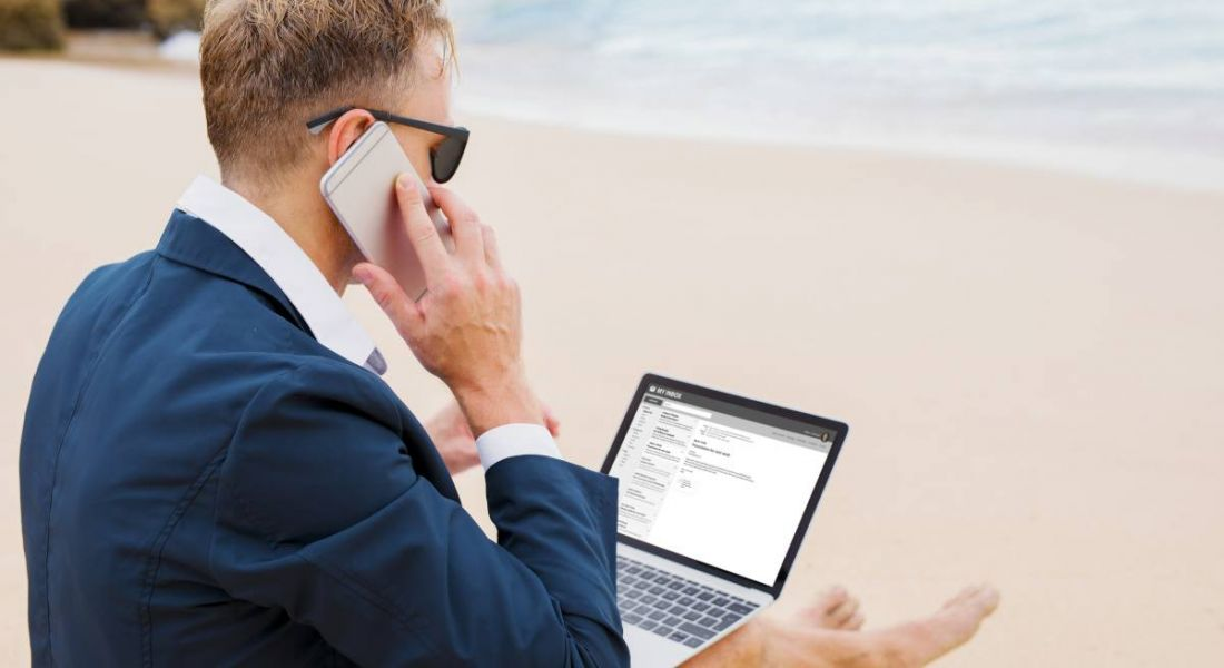 Businessman working on beach, wearing a suit while using his phone and his laptop.