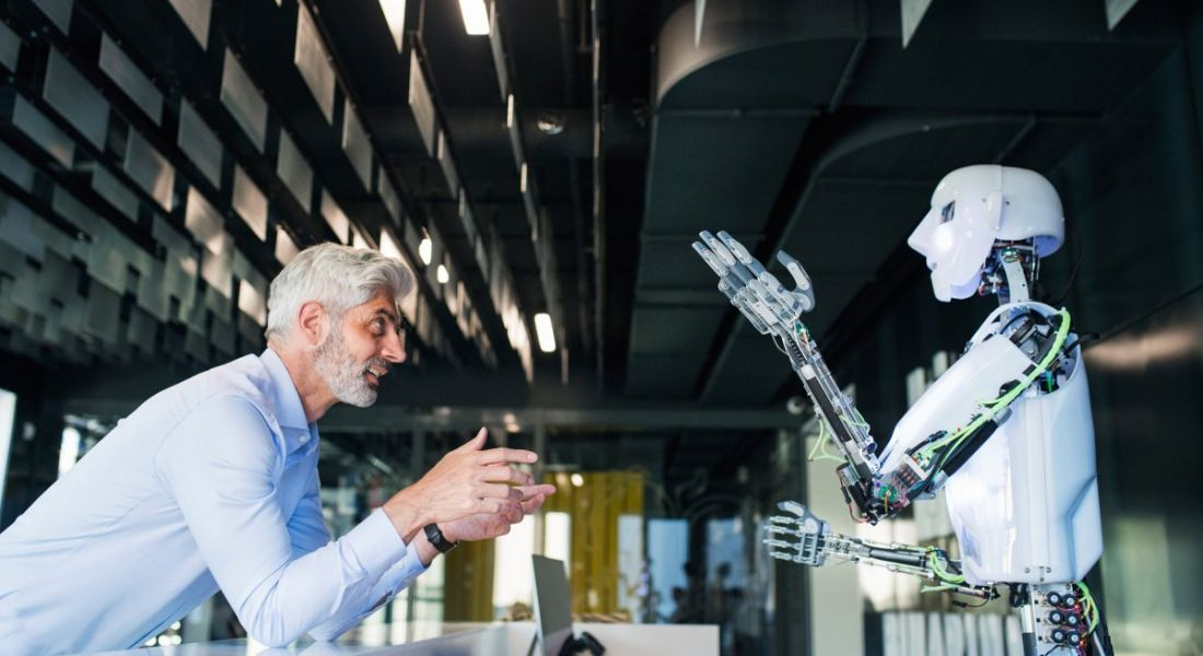 A professional man with gray hair is speaking with a robot at work.