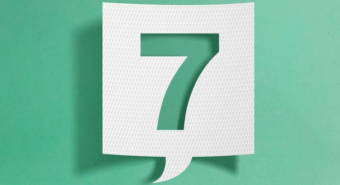 A slip of white paper cut into the shape of a speech bubble, with the number seven cut out from the centre, on a turquoise background.