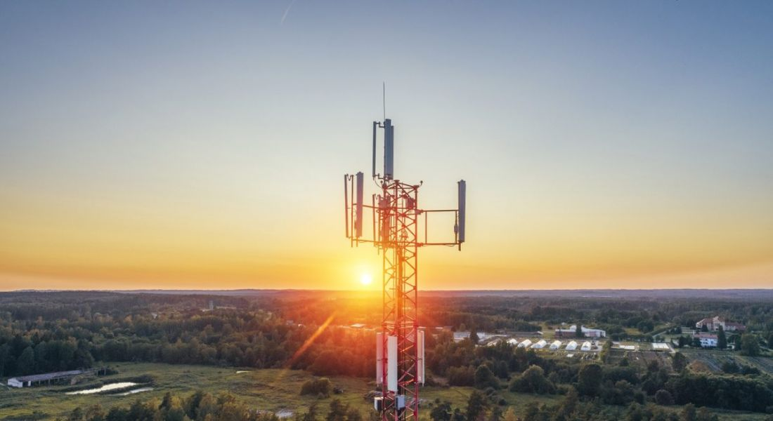 View of telecoms tower against cloudless sky at sunrise.