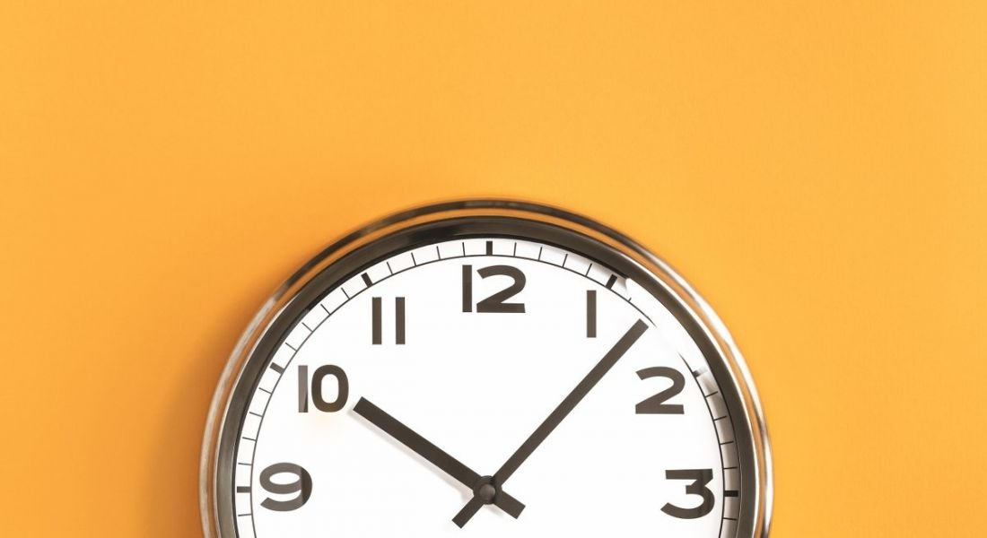 Top half of an analogue clock at seven minutes past 10, against a crisp orange background.