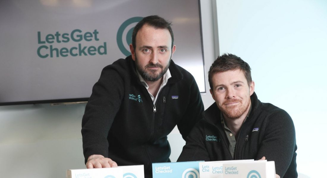 Two young men in black sweaters sitting at a table with LetsGetChecked turquoise logo in the background.
