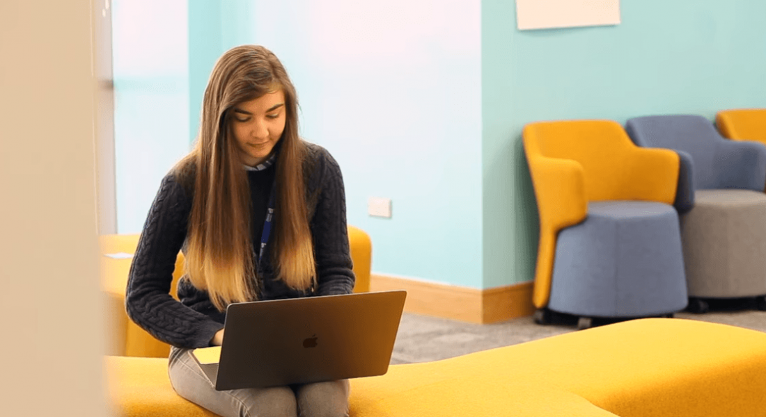 A young woman is sitting on a colourful yellow couch and working on her laptop in Liberty IT.