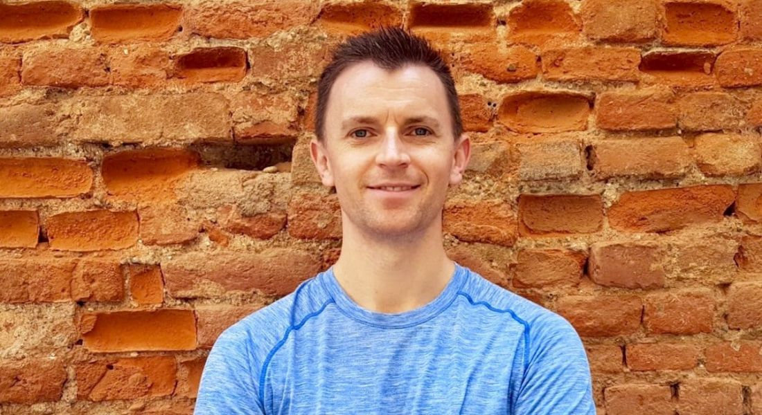 A man in a blue T-shirt is smiling into the camera in front of a redbrick wall.