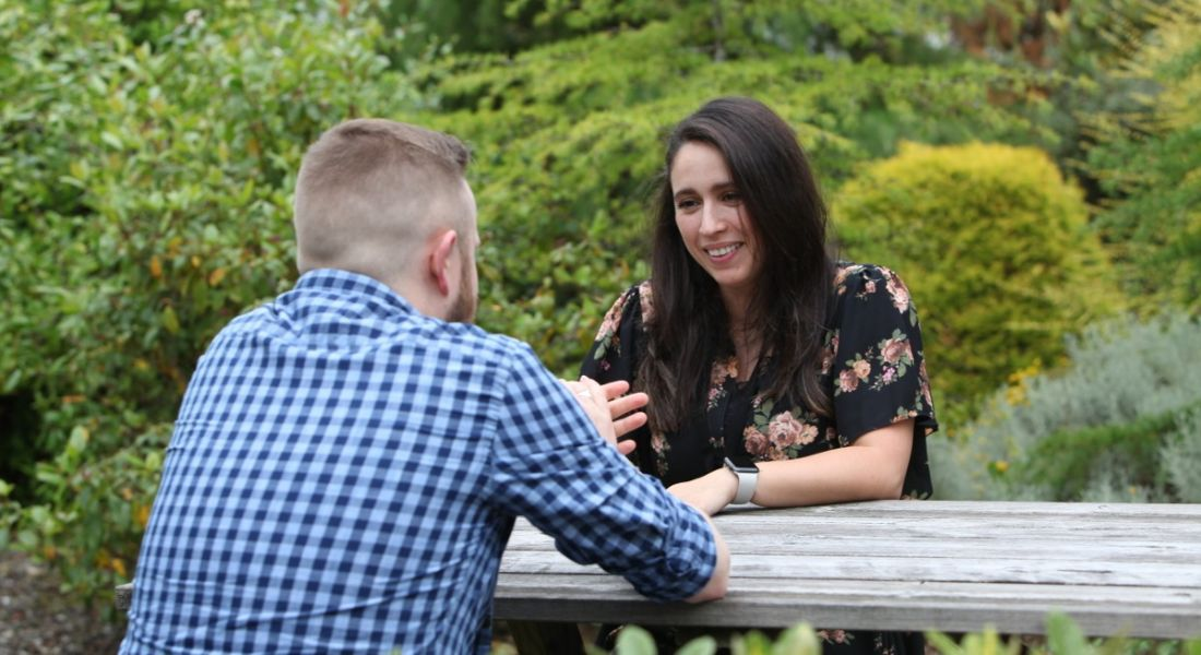 A man and woman at Kemp are talking to each other at a wooden picnic table outdoors, with trees in the background.