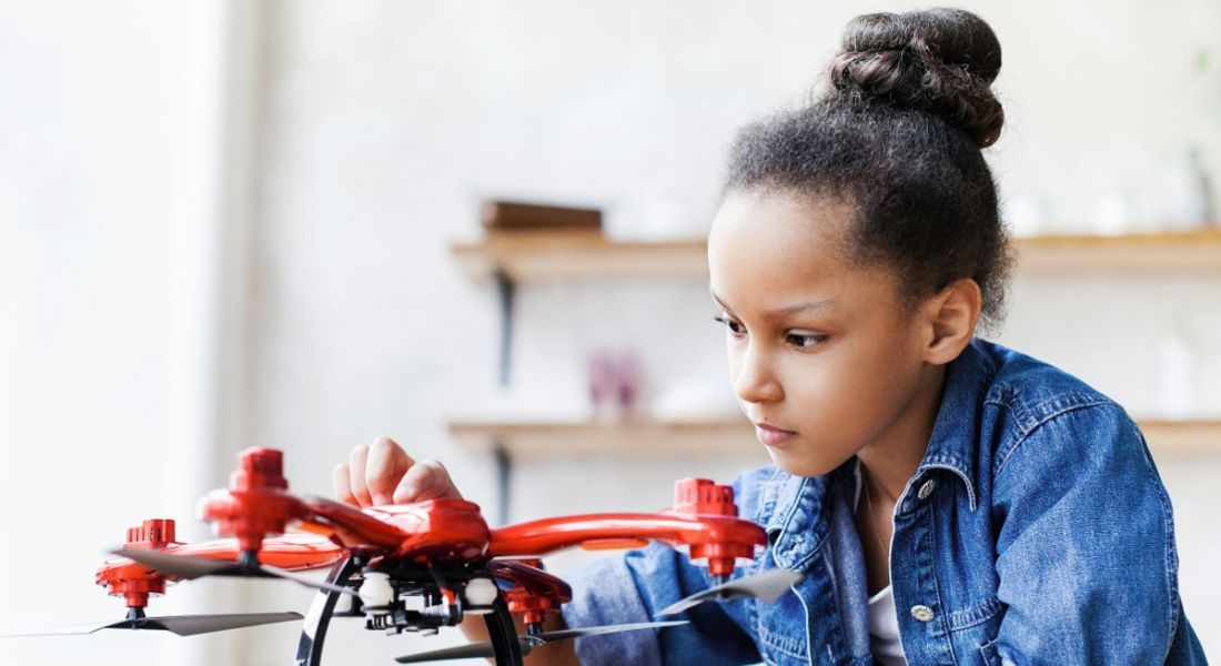 Young girl in denim shirt playing with a drone.