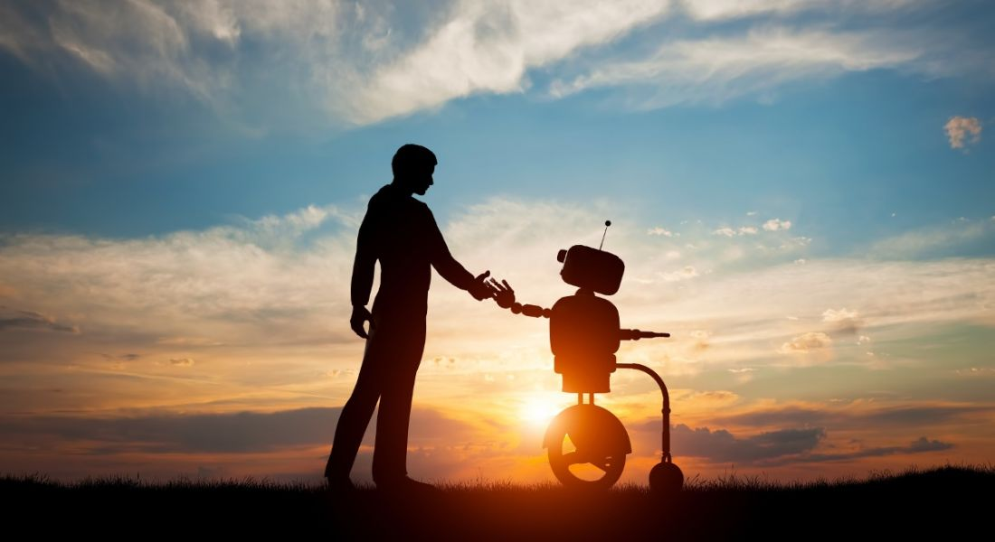 Man and robot meet and shake hands against sunset.