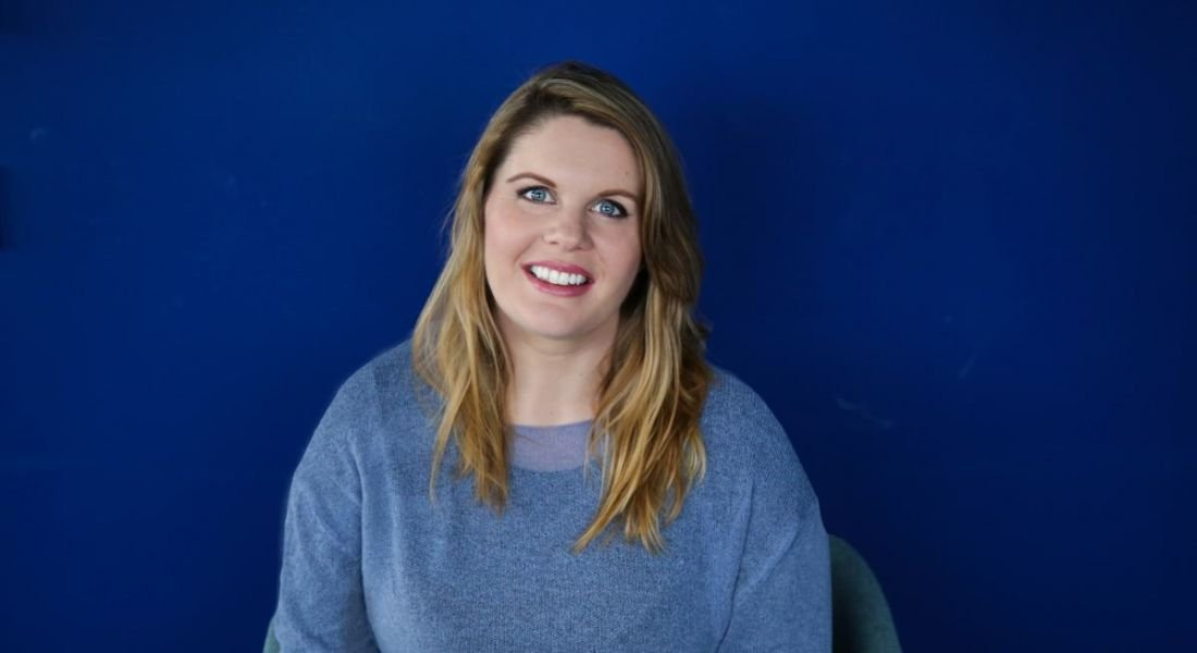 Louise Ryan, working in product design at Workhuman, is smiling into the camera against a blue background.
