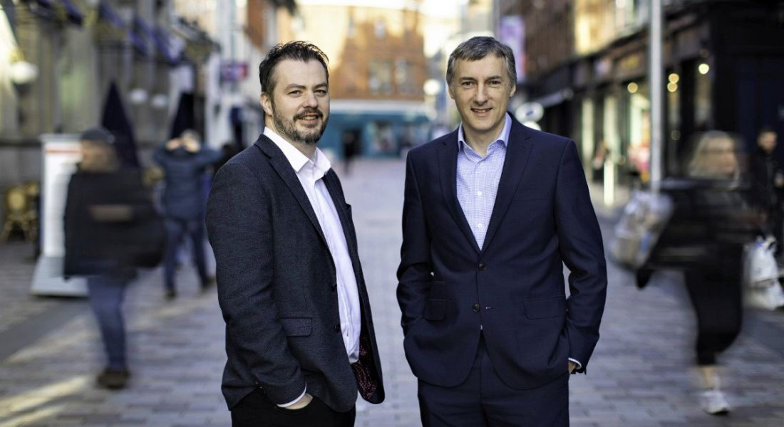Two professional men in suits are smiling into the camera, standing on Queen's Street in Belfast.