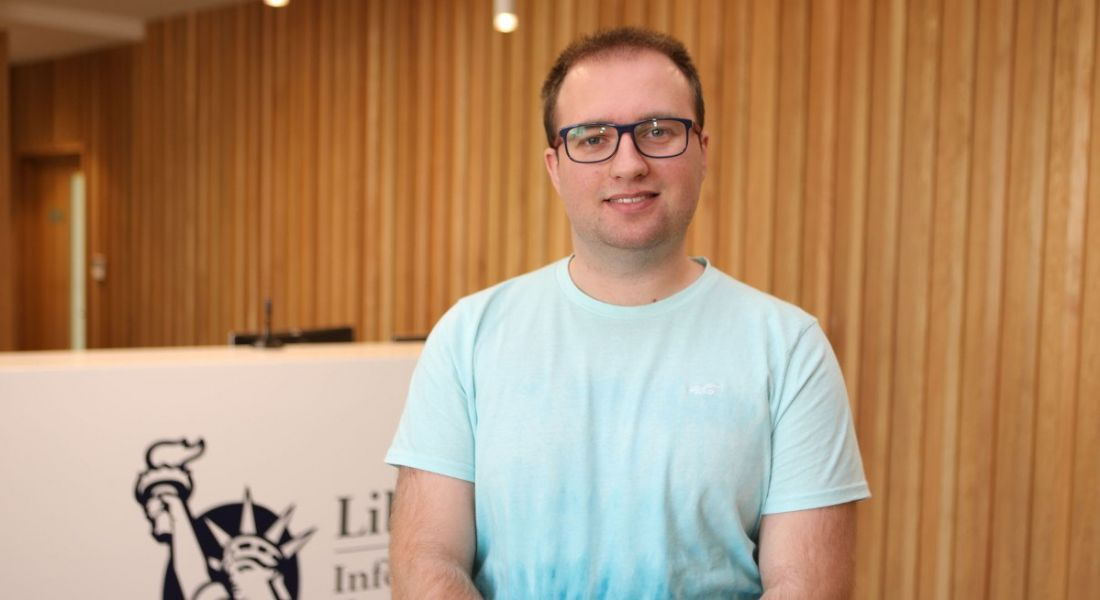 A young professional man in casual clothing is smiling into the camera at the reception area in Liberty IT.