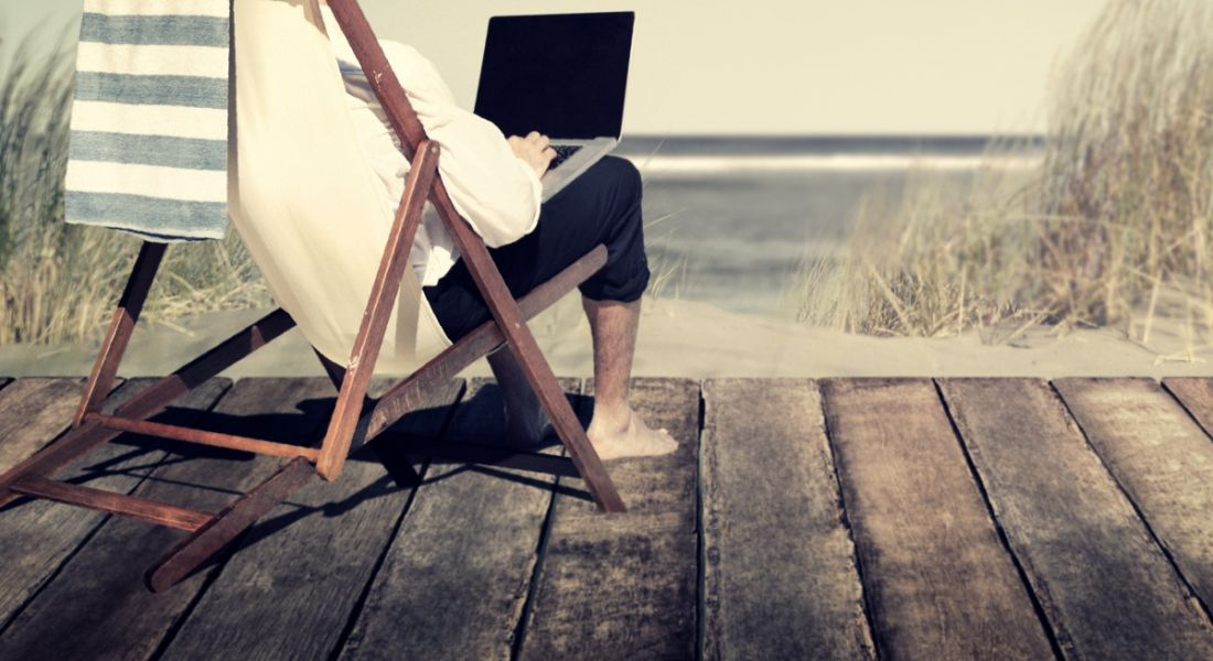 Person sitting in a deckchair on decking at a beach, wearing a white sweater and working on a laptop.
