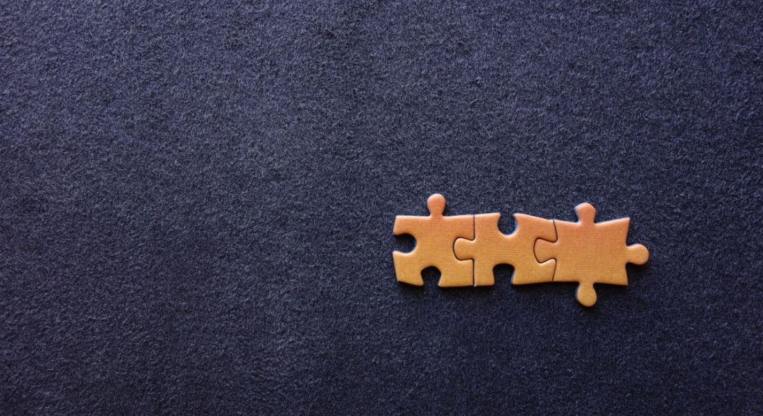 Three orange puzzle pieces stuck together, sitting on a dark blue background.
