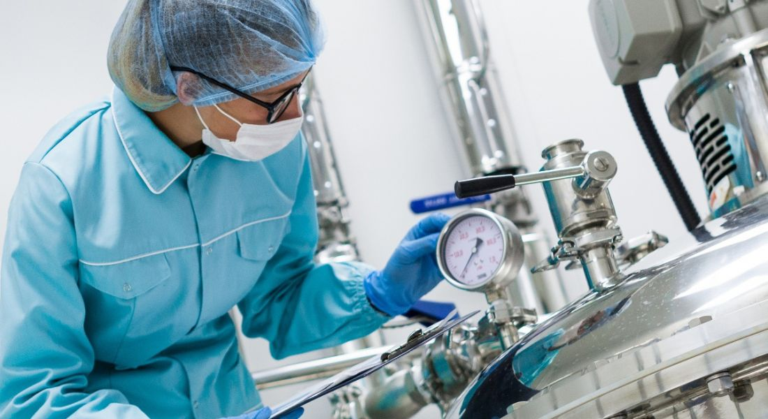 Scientist working with large vat in the lab at a pharmaceutical manufacturing company.