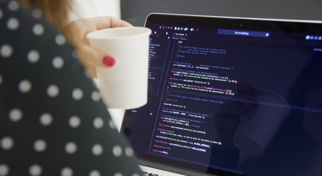 Woman in a spotted top holding a coffee cup and working on code at a computer.