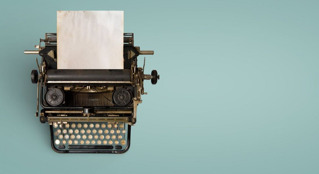 Vintage typewriter header with old paper on a teal background.