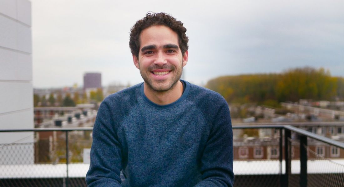 A young professional man in casual clothing is sitting on a balcony smiling into the camera at MessageBird offices in Amsterdam.