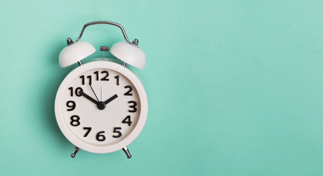 Vintage alarm clock isolated on pastel mint background.