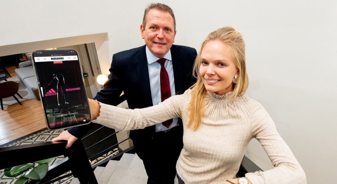 A professional man and a professional woman are standing and smiling into the camera, holding a tablet showing Adidas branding with Smartzer technology.