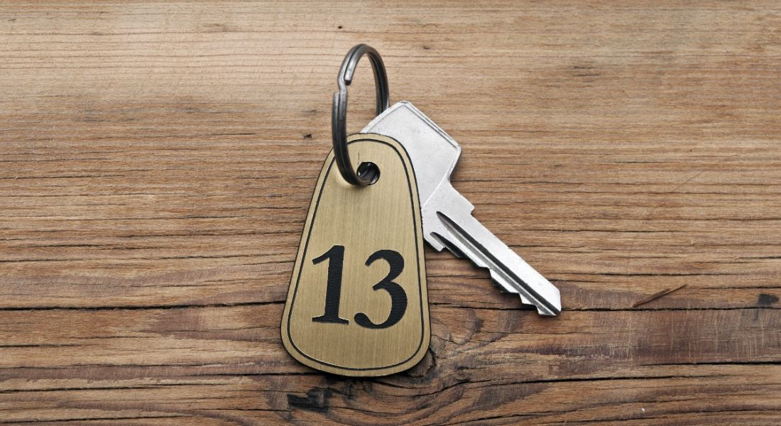 Close-up of a key with a tag reading the number 13, sitting on a wooden desk.