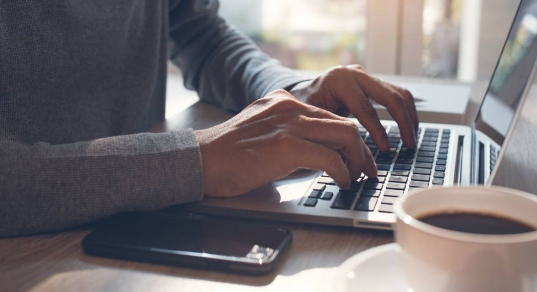 Hands typing on a laptop keyboard with mobile smartphone on office desk at home, working freelance.