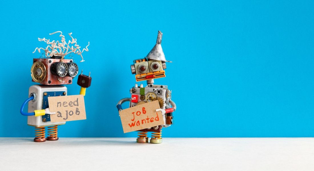 Two toy robots against a blue background holding signs reading job wanted, symbolising automation.