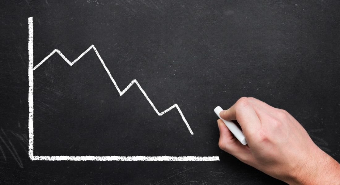 A white graph is being drawn on a blackboard in chalk, with the trend falling downwards.