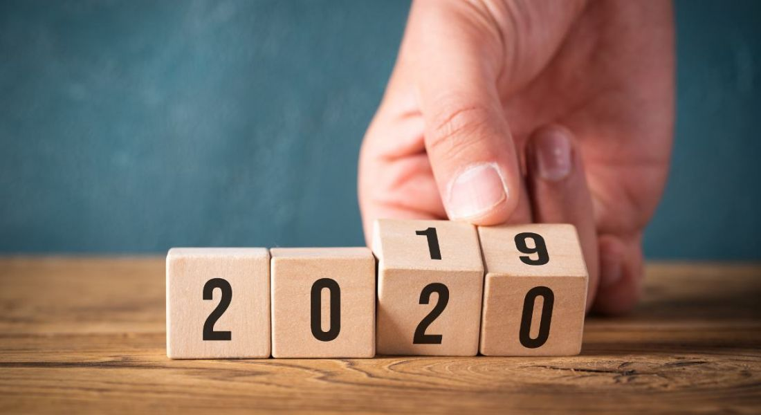 Hand flipping wooden cubes from year 2019 to 2020.
