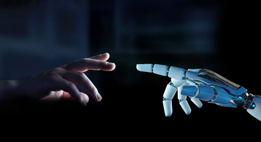 White cyborg finger about to touch human finger, against a dark background.