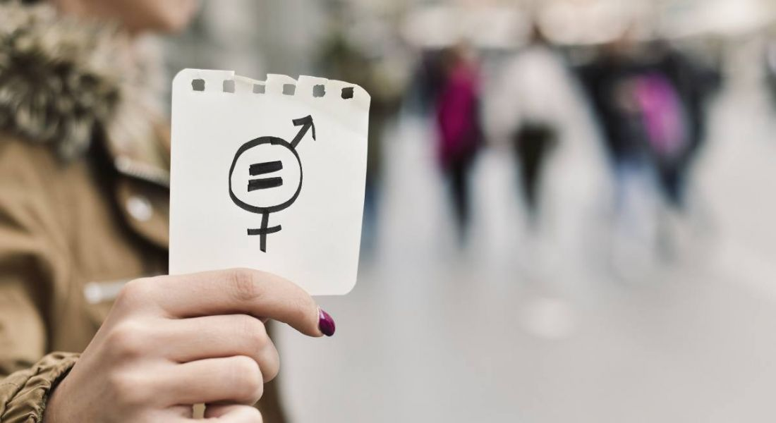 Close-up of a person's hand in the street, showing a piece of paper with a symbol for gender equality drawn on it.