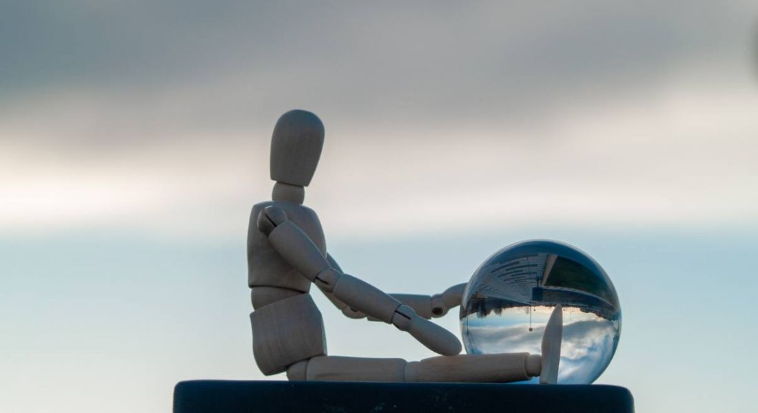 Wooden mannequin sitting against a sky backdrop with a crystal ball.