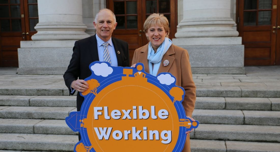 A man and woman are standing outside a government building on steps, holding a bright sign reading 'flexible working'.
