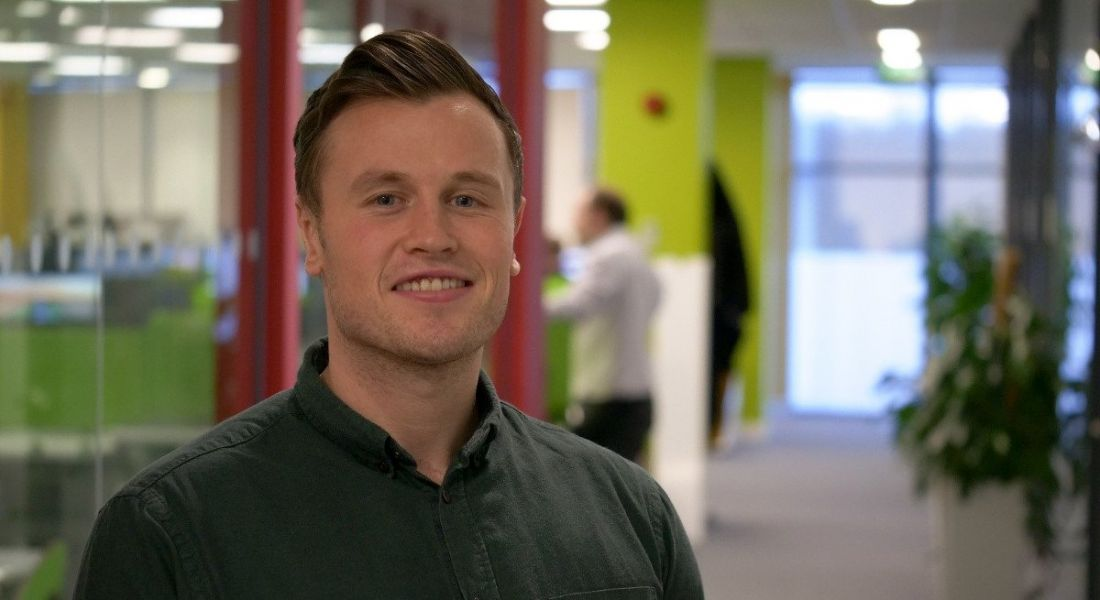 A young professional man is standing in a hallway at Genomics Medicine Ireland, smiling into the camera.