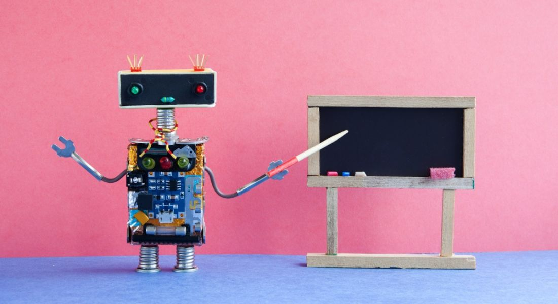 A toy robot is teaching using a blackboard in a colourful classroom setting.