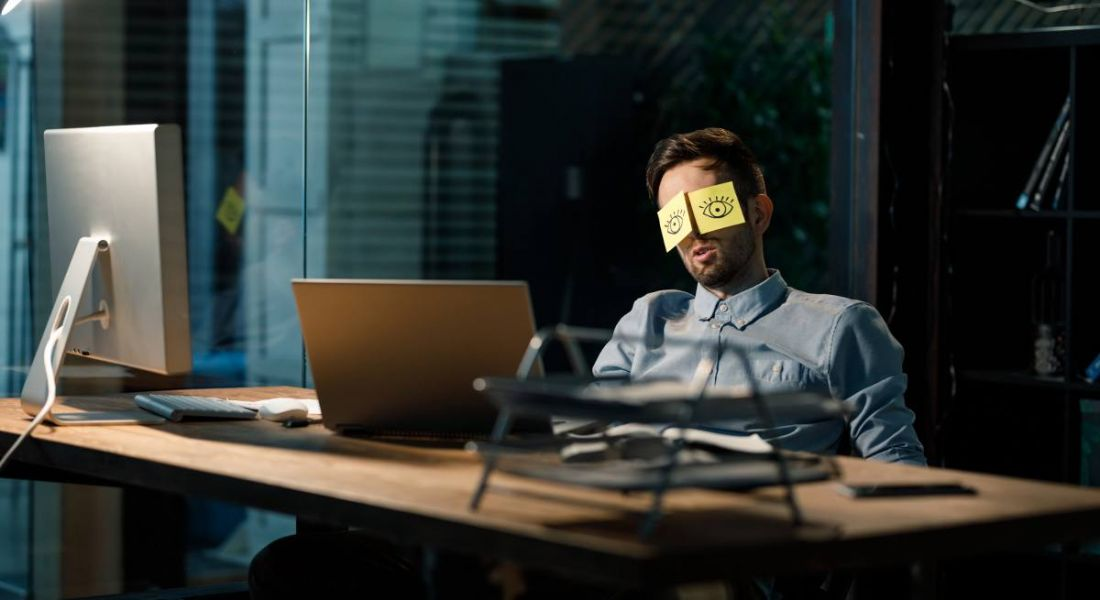 A man sleeping in a dark office, sitting at a table with his eyes covered by stickers that have eyes drawn onto them.