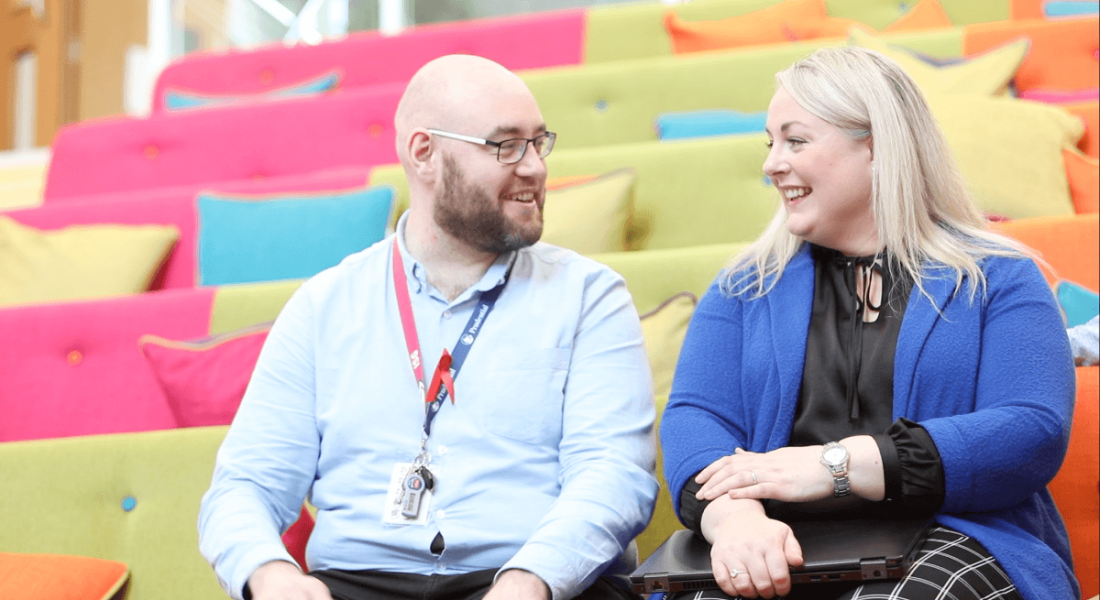 A professional man and woman who drive the Pride business resource group at Pramerica are sitting on colourful seats at the company's Letterkenny office, smiling at each other.