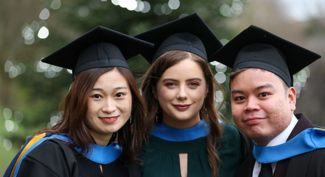 View of young students in gowns and mortar boards standing outside with foliage in the background.
