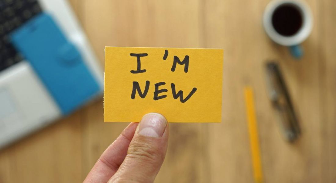 A person holding a card that reads 'I'm new' at an office.