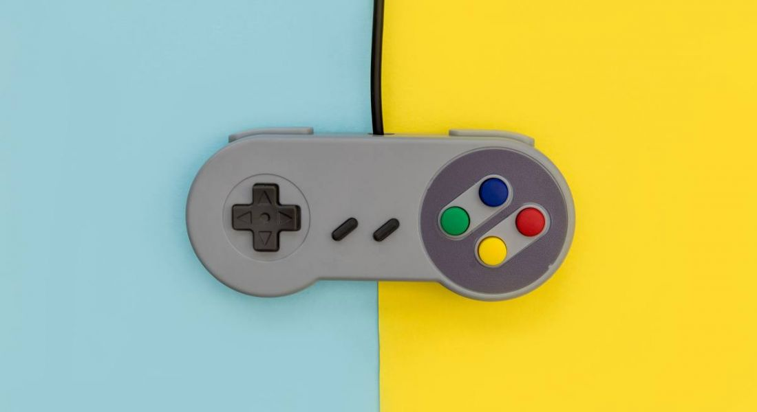 Retro video games controller on yellow and blue background.